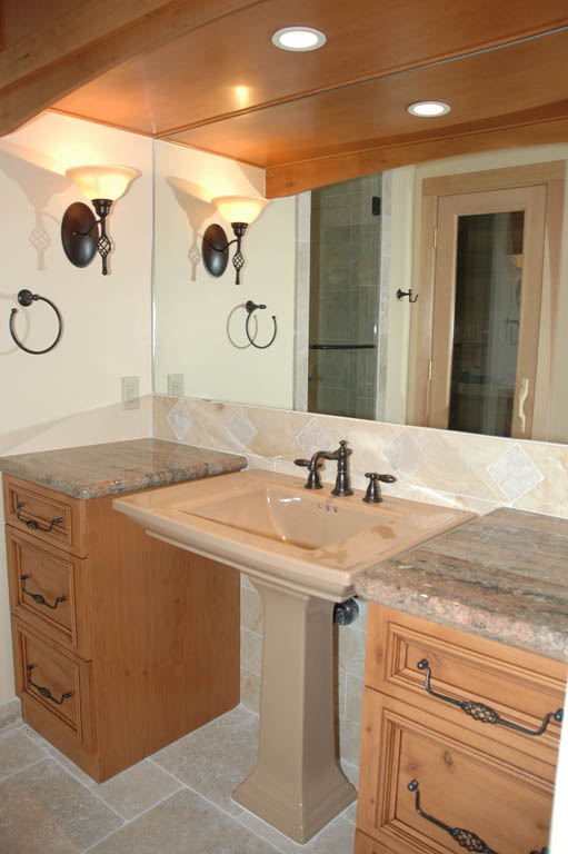 pedestal sink uniquely placed between two cabinets